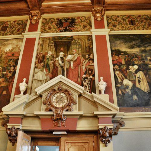 muurschilderingen van Karel Boom, die het gerecht ten tijde van Maria van Hongarije voorstellen.