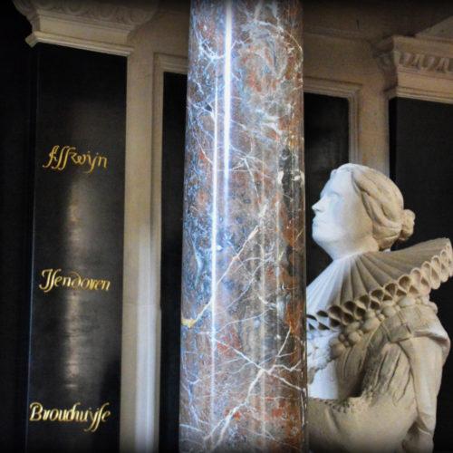 gekleurd marmeren monument met door zuilen gedragen overhuiving waaronder de knielende figuren van gouverneur Willem van der Reydt Broeckem en Judith van Aeswijn, opgericht in 1625;